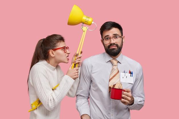 Der horizontale schuss eines unzufriedenen verärgerten studenten trägt eine lampe, beißt die zähne zusammen und sieht den klassenkameraden irritiert an