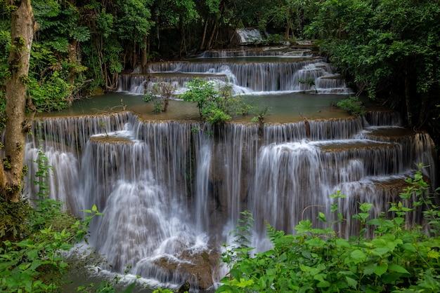 Der hua mea khamin wasserfall hat tropische bäume, farne, die im morgenlicht am wasserfall wachsen, kühles, frisches wetter und einen ruhigen ort zum entspannen im dschungel. karnchanaburi, thailand.