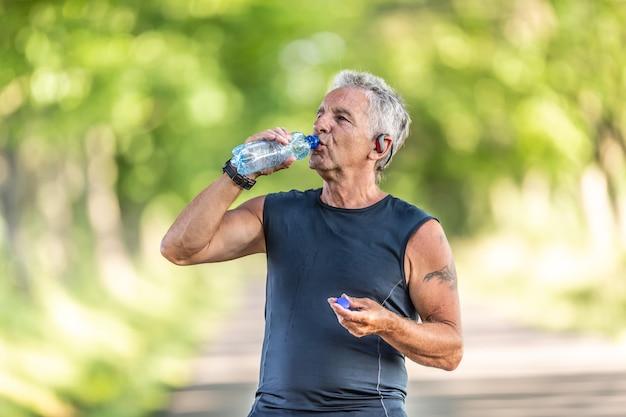 Der hübsche ältere mann rehydriert nach einem lauf im freien in der natur, indem er wasser aus einer flasche trinkt.