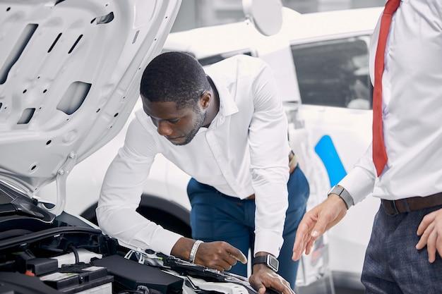 Der hübsche afrikanische geschäftsmann untersucht ein auto, bevor er es kauft