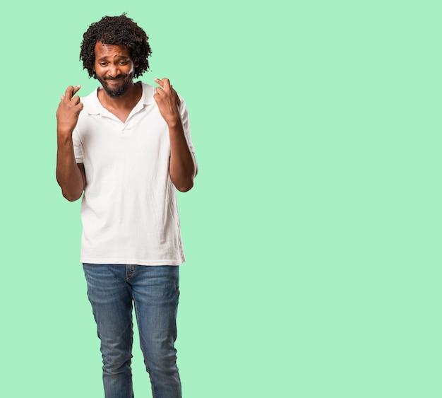 Der hübsche afroamerikaner, der seine finger kreuzt, möchte für zukünftige projekte glücklich sein