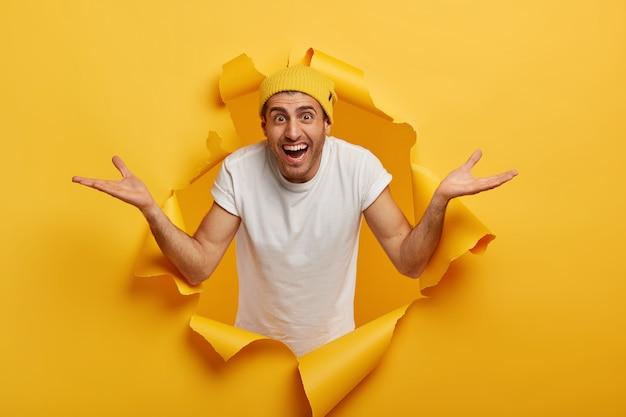 Der hübsche ahnungslose junge mann hat einen fröhlichen ausdruck, spreizt die handflächen mit fragendem blick, zögert, trägt einen gelben hut und ein weißes t-shirt