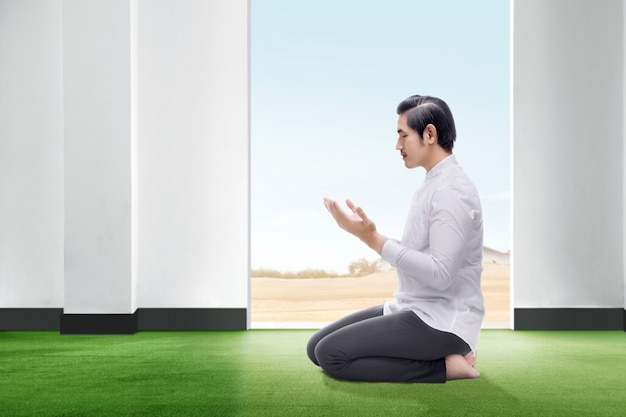Der hübsche asiatische mann, der in betender position sitzt, schließen seine augen und heben die hände auf dem teppich innerhalb des raumes an