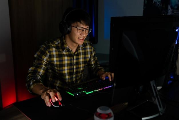 Der hübsche, aufgeregte asiatische spieler mit kopfhörern genießt und freut sich, während er videospiele am computer in einem gemütlichen raum spielt. er wird mit warmem neonlicht, spiel- und technologie-e-sport-konzept beleuchtet.