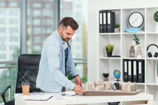 Der hübsche bärtige architekt, der an einem bauprojekt arbeitet, untersucht das modell, an dem er arbeitet