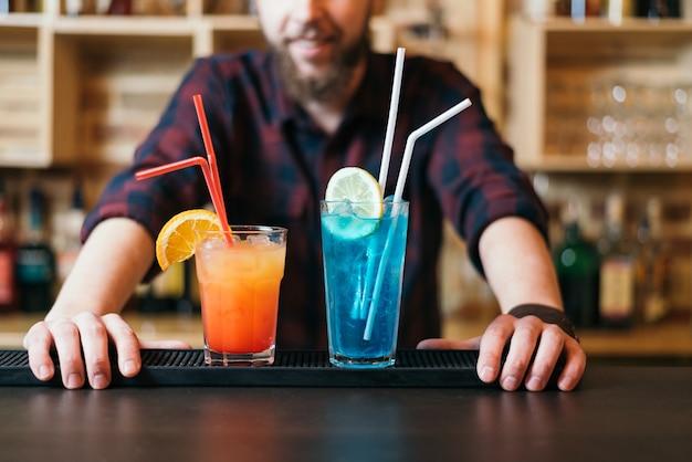 Der hübsche bärtige barmann macht im nachtclub blaue lagune und tequila-sonnenaufgang-cocktail. selektiver fokus auf brille.