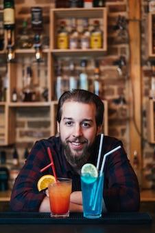 Der hübsche bärtige barmann macht im nachtclub blaue lagune und tequila-sonnenaufgang-cocktail.