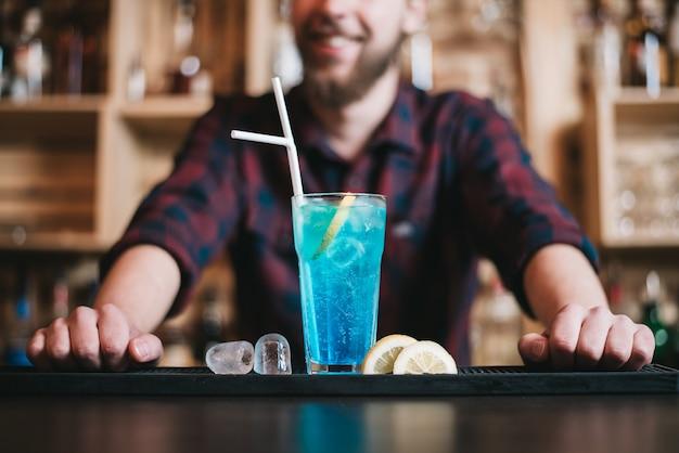 Der hübsche bärtige barmann macht im nachtclub einen blauen lagunencocktail. selektiver fokus auf glas.