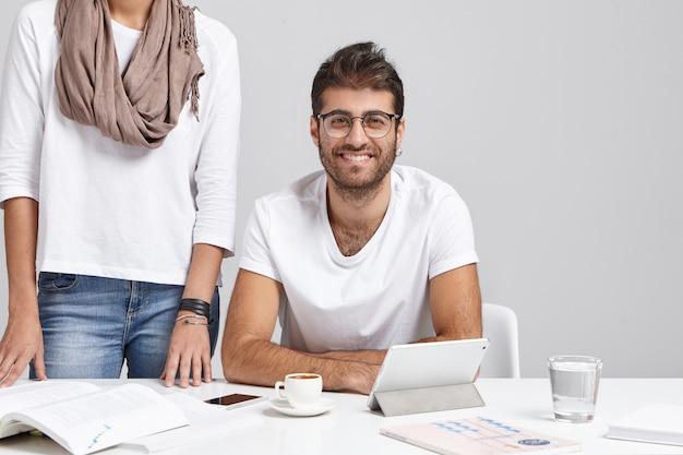 Der hübsche bärtige unternehmer und seine nicht wiedererkennbare sekretärin arbeiten beim projekt zusammen