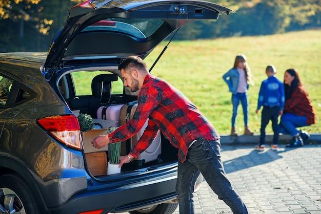 Der hübsche bärtige vater lädt gepäck in den kofferraum, der auf eine familienurlaubsreise geht.