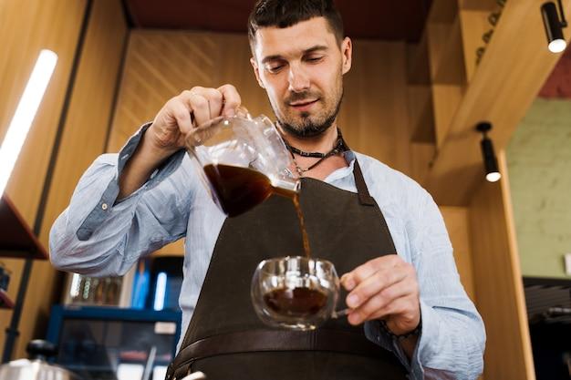 Der hübsche barista gießt aromatisierten kaffee in eine glaskanne im café
