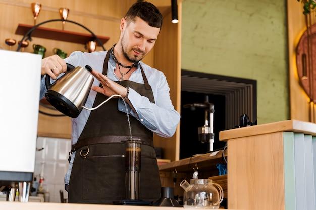 Der hübsche barista gießt heißes wasser in die aeropresse mit kaffee im café