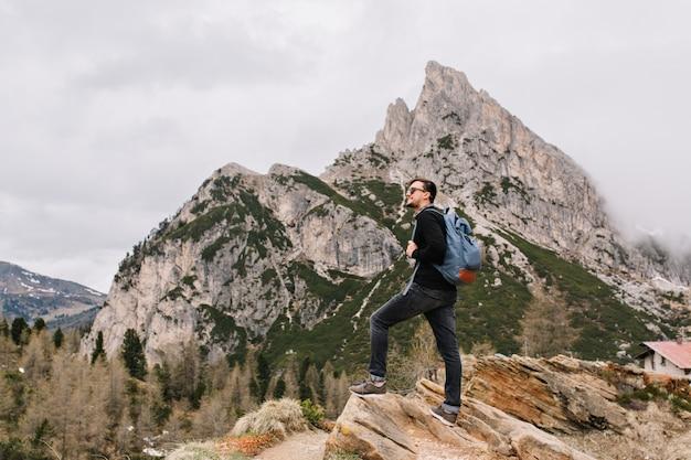 Der hübsche brünette mann steht auf dem felsen und betrachtet bewundernd erstaunliche naturansichten