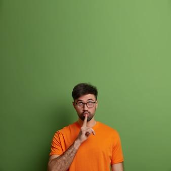 Der hübsche erwachsene mann bittet darum, ruhig zu bleiben, legt den finger auf den mund, konzentriert sich oben, erzählt geheime informationen, macht eine leise geste, gekleidet in ein lässiges orangefarbenes t-shirt, isoliert auf einer grünen wand, kopiert platz nach oben