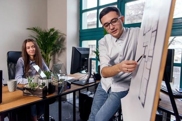 Der hübsche firmenmanager mit brille erklärt seinen mitarbeitern die arbeitsaufgaben. kreative menschen oder werbegeschäftskonzept. zusammenarbeit. junge schöne leute, die zusammen im büro arbeiten.