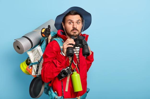 Der hübsche junge männliche tourist hält ein fernglas, geht im wald spazieren, trägt freizeitkleidung, trägt die notwendigen dinge zum reisen und verbringt gern urlaub in aktiver kleidung