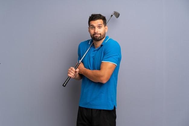 Der hübsche junge mann, der das golf macht zweifel spielt, gestikulieren beim anheben der schultern
