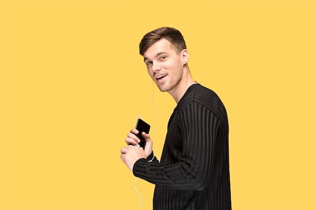Der hübsche junge mann, der steht und musik hört. attraktiver mann, der kopfhörer und handy auf gelbem studiohintergrund hält