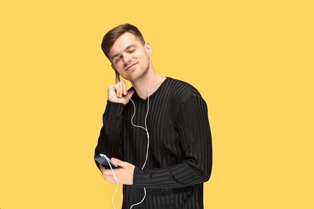 Der hübsche junge mann, der steht und musik hört.