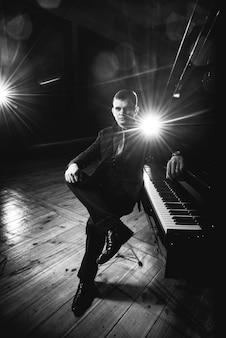 Der hübsche junge mann im anzug sitzt am klavier und macht klaviermusik. schwarz-weiß-foto