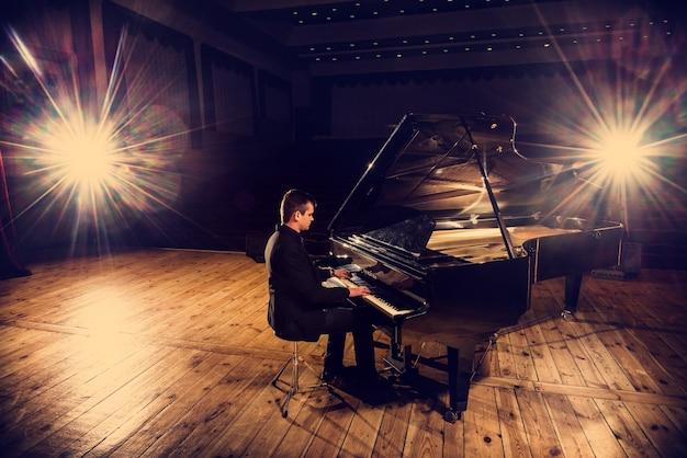 Der hübsche junge mann im anzug sitzt am klavier und macht klaviermusik.