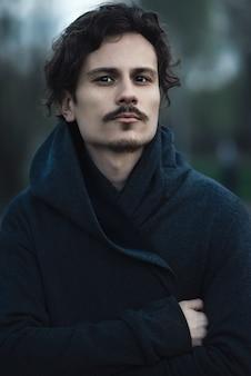 Der hübsche junge mann mit den lockigen haaren befindet sich jetzt tief in seiner seele.