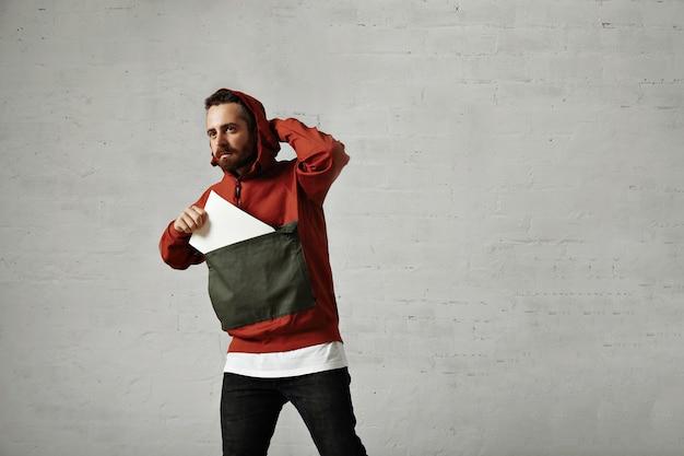 Der hübsche junge mann passt die kapuze seines stilvollen anoraks an und holt ein leeres stück papier aus der vordertasche