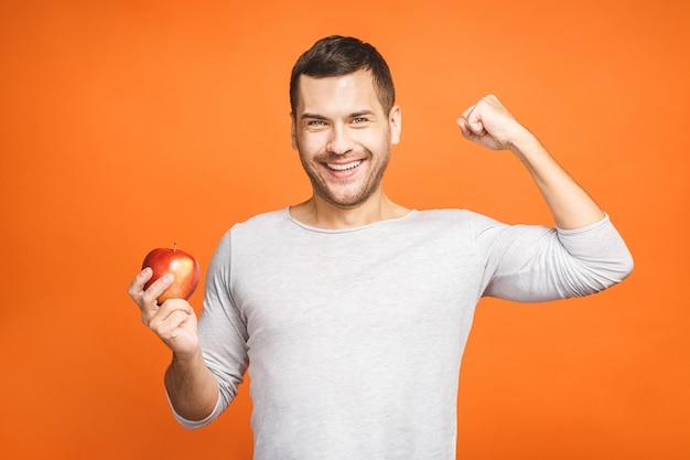 Der hübsche junge sportler zeigt seine muskeln mit einem apfel und lächelt.