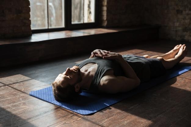 Der hübsche junge starke sportler im fitnessstudio liegt auf dem boden