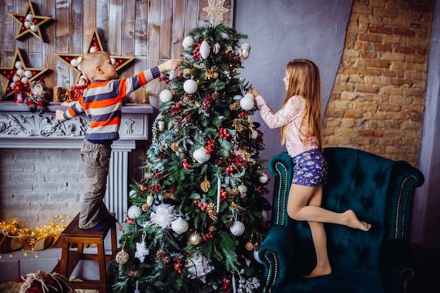 Der hübsche junge und das mädchen, die einen weihnachtsbaum schmücken