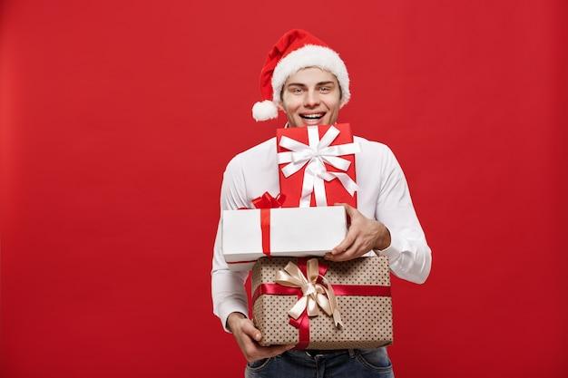 Der hübsche kaukasische glückliche geschäftsmann, der viele geschenke mit dem abnutzungs-sankt-hut hält, der auf weiß aufwirft, lokalisierte hintergrund.