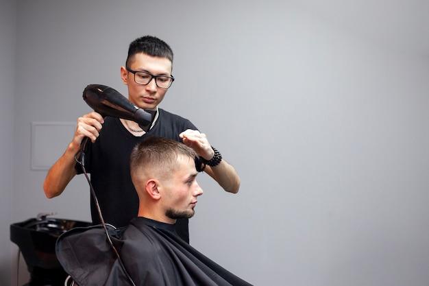 Der hübsche kerl hat einen haarschnitt in einem friseurladen