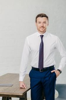 Der hübsche männliche büroangestellte, der in der gesellschaftskleidung gekleidet wird, hält eine hand in der tasche