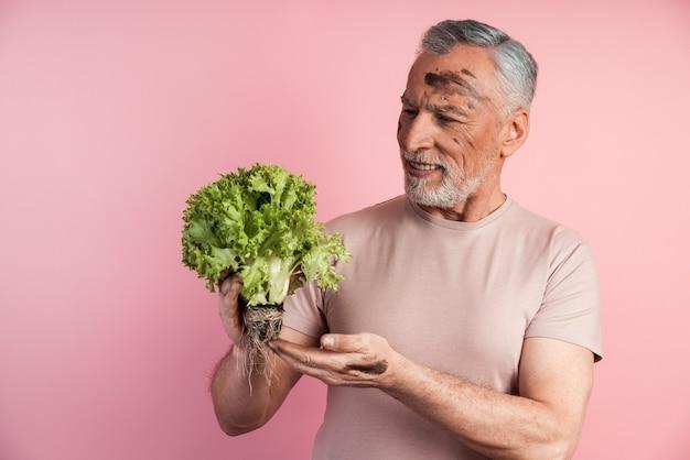 Der hübsche mann hält eine handvoll salatblätter in der hand und sieht ihn an
