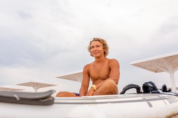 Der hübsche mann sitzt am strand mit dem weißen leeren surfbrett und wartet auf die welle, um am meeresmeerküste zu surfen