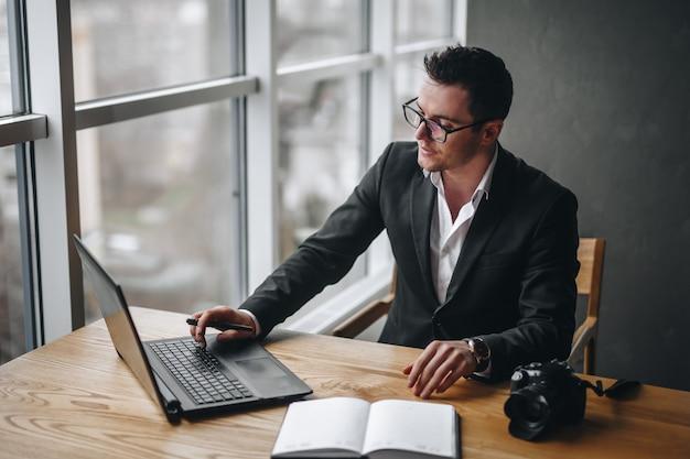 Der hübsche und junge fotograf nimmt eine bestellung vom brautpaar entgegen und sitzt in einer schwarzen jacke im büro