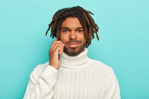 Der hübsche unrasierte mann hält ein modernes mobiltelefon in der nähe des ohrs, führt telefongespräche, trägt einen warmweißen pullover, hat einen bart und dreadlocks