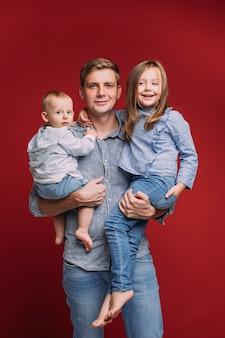 Der hübsche vater hält zwei seiner kinder an den händen