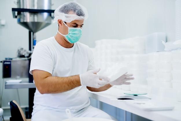 Der hübsche wissenschaftsforscher mit maske überprüft sein produkt.