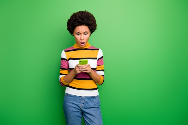 Der hübschen bloggerin dunkle haut lockige dame, die telefonhände hält und schreckliche falsche nachrichten über sich selbst liest