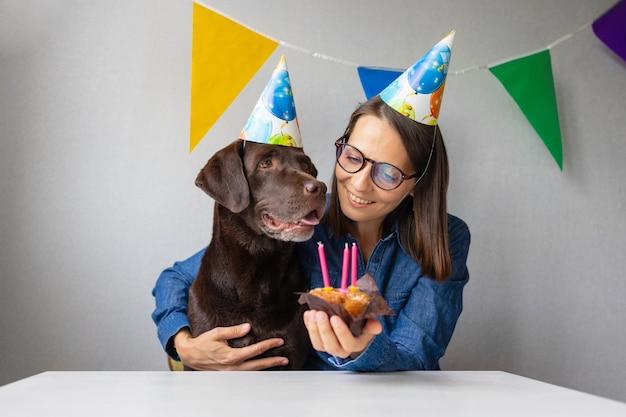 Der hundegeburtstag der feiertag ist der geburtstag eines haustierkerzen und eines kuchens für einen labrador-retriever