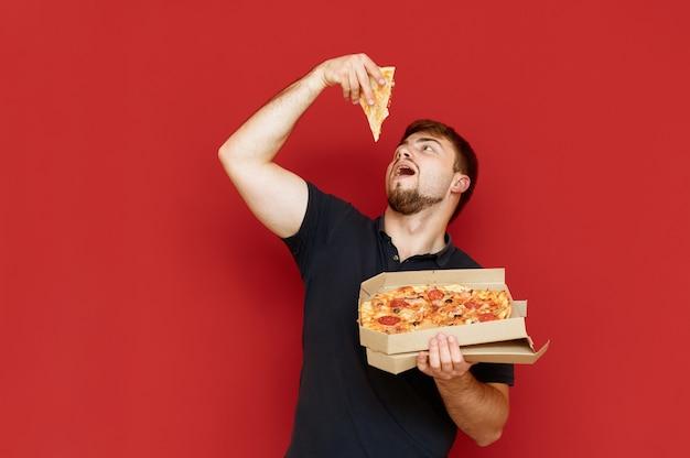 Der hungrige lustige mann steht auf und nimmt ein stück pizza aus der schachtel