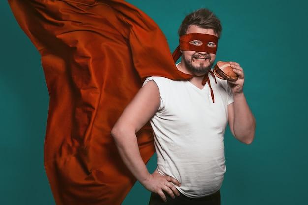 Der hungrige superheld, der einen hamburger, superhelden oder antihelden in einem roten anzug mit einem fliegenden umhang isst, isst fast food und schaut in die kamera. auf grünem hintergrund ausschneiden