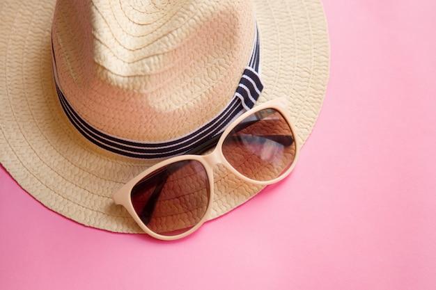 Der hut der strohstrandfrau mit sonnenbrillen auf rosa ebenenlage. ansicht von oben. sommerausflug.