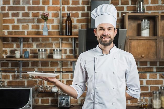 Der hut des glücklichen kochs tragender chef, der in der hand eine leere platte hält