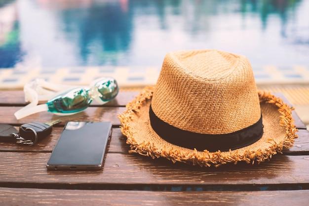 Der hut wird auf der holztischseite des swimmingpools mit smartphone und schutzbrille platziert. im vintage-stil