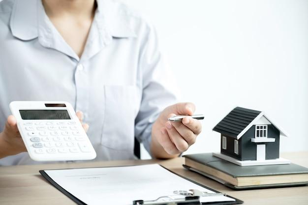 Der immobilienmakler erklärt dem weiblichen käufer den geschäftsvertrag, die miete, den kauf, die hypothek, ein darlehen oder die hausversicherung.