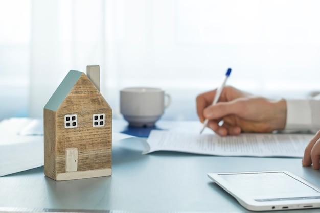Der immobilienmakler unterzeichnet die transaktionsdokumentation während. ein haus kaufen hypothek.