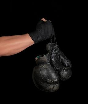 Der in einen schwarzen elastischen sportverband gewickelte arm hält zwei alte vintage-boxhandschuhe aus leder