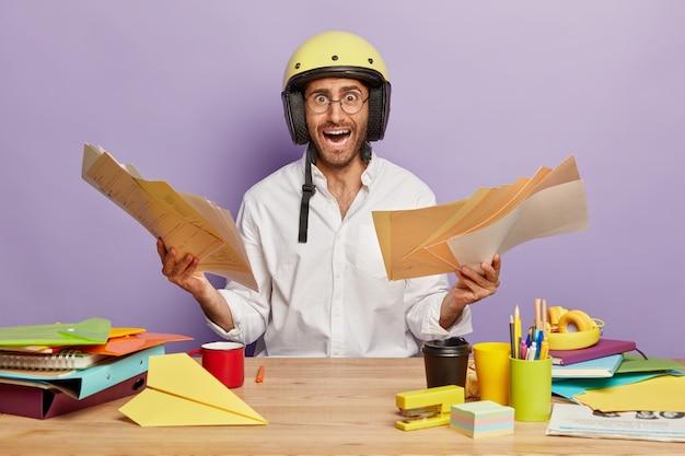 Der in panik geratene junge mann arbeitet mit dokumenten in seinem schrank, ruft unzufrieden aus, trägt ein elegantes weißes hemd und einen helm